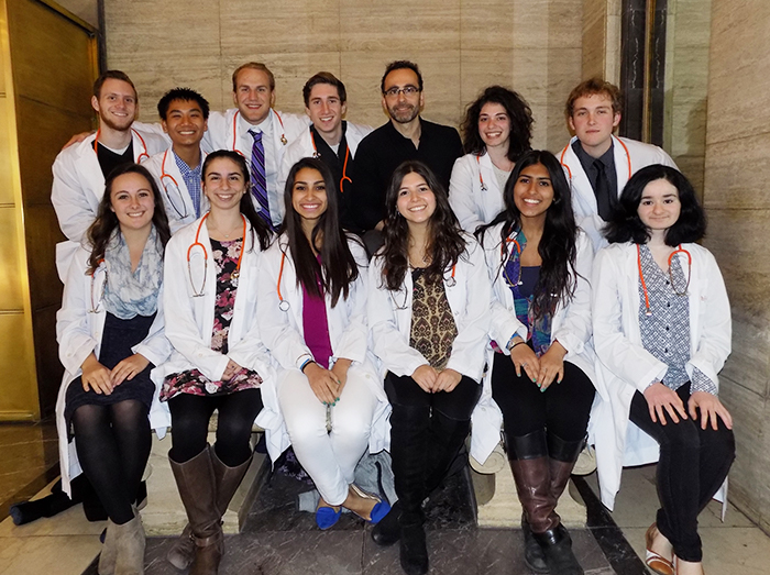 A group of medical students wearing white coats sit in two rows for a group photo