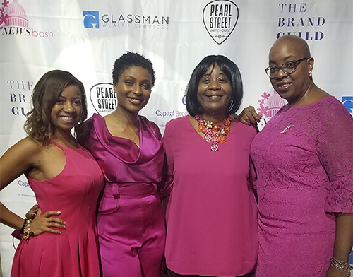 Four women wearing pink stand side by side at the event.