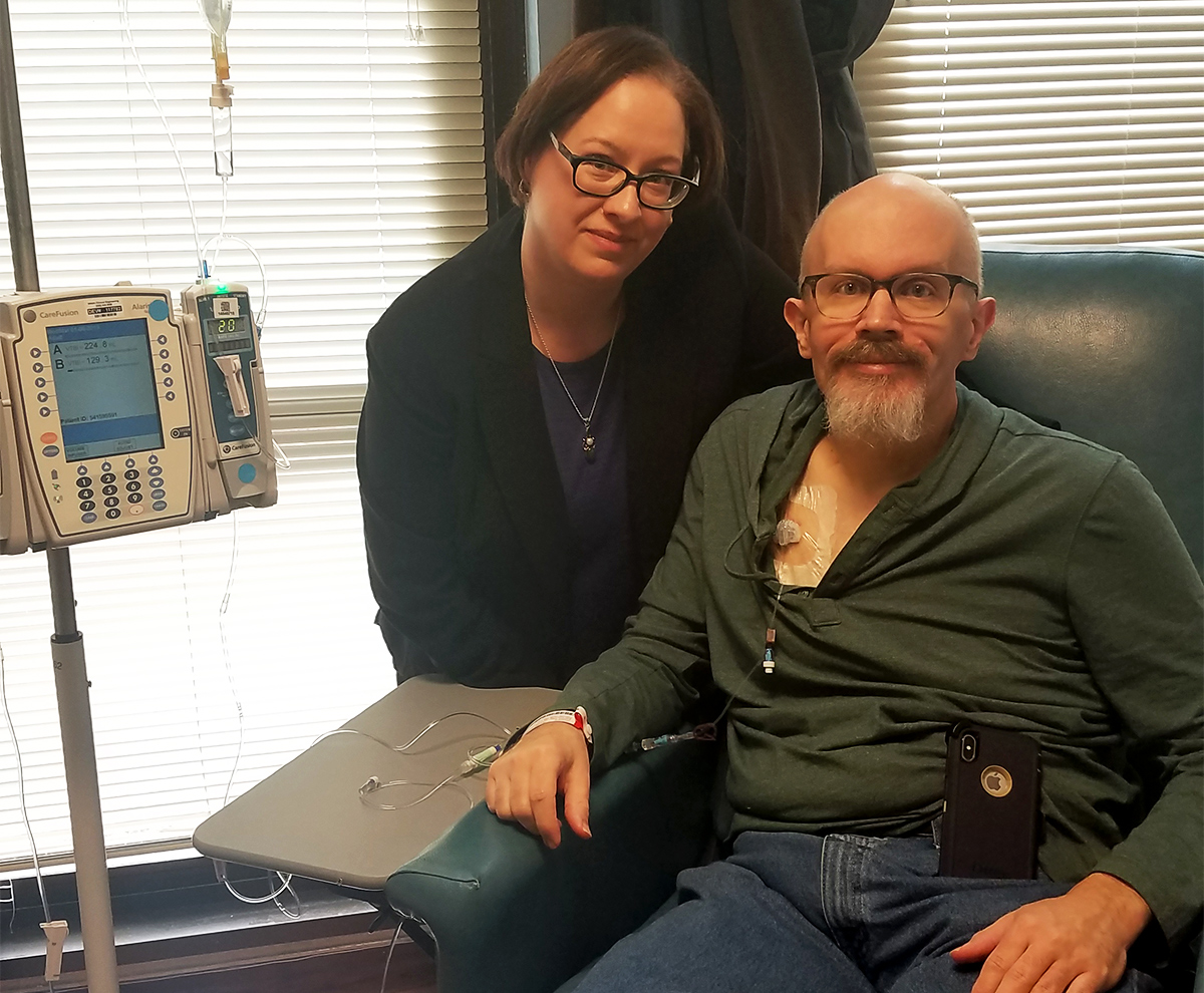 A woman sits next to a man in a chair who is receiving chemotherapy