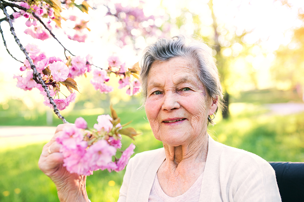 An older woman poses with pink tree blossoms