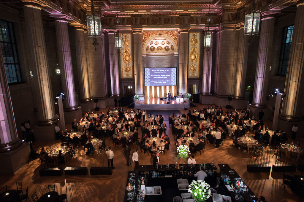 A large room is filled with tables and people for an event.