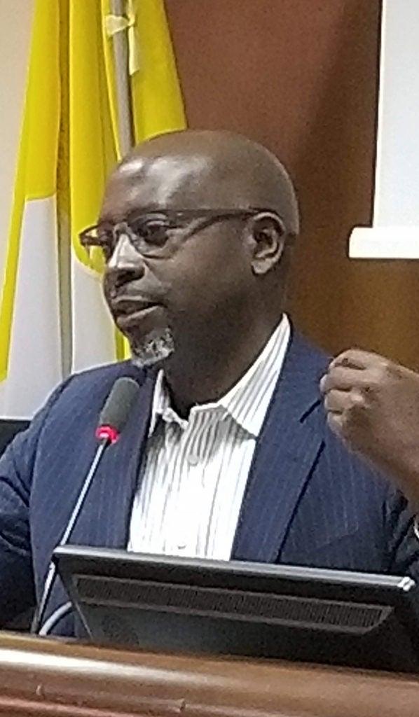 Deus Bazira speaks at a podium