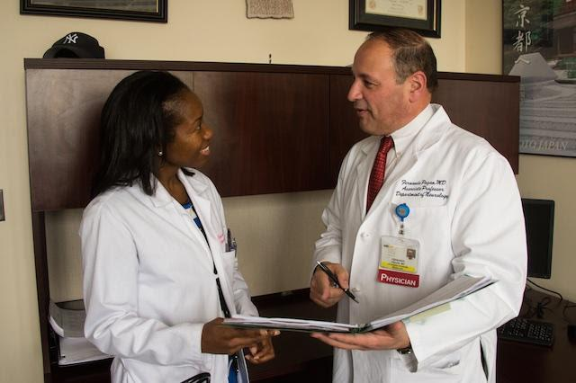 Two doctors talk while holding a clipboard