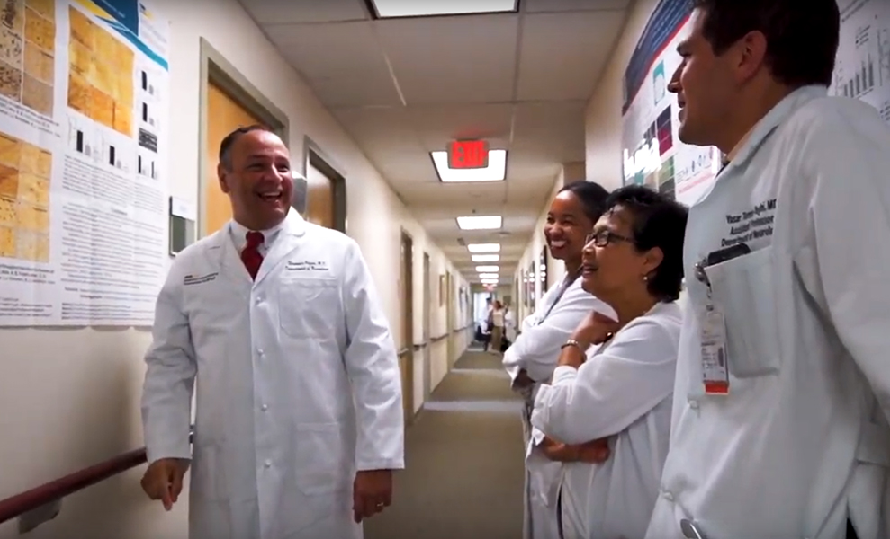 Several physicians in white coats stand in a hallway talking