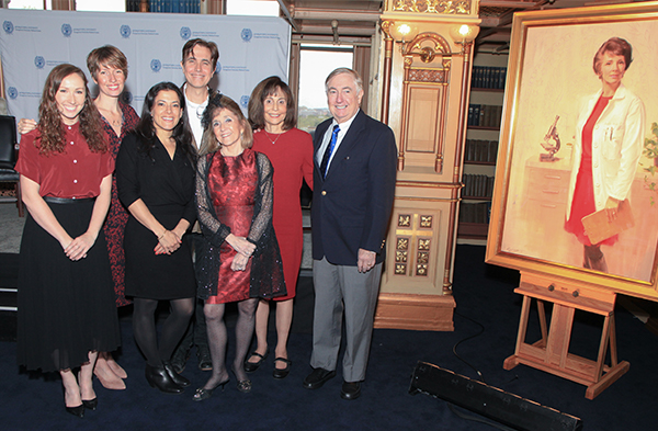 Members of the Ramey family stand together next to the portrait of Estelle Ramey, MD