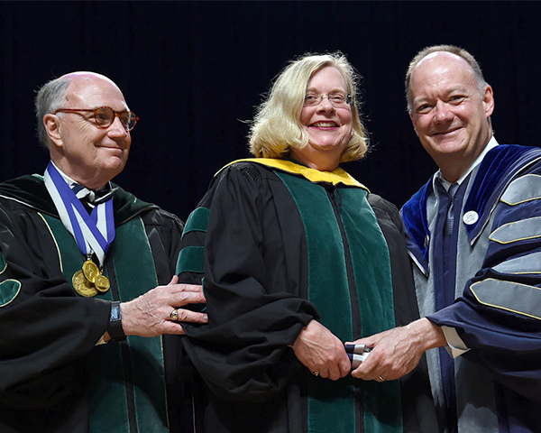 Dr. Hingle is flanked by Dr. MItchell and  President DeGioia