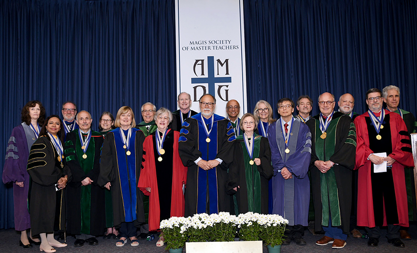 A group of people in academic regalia stand onstage