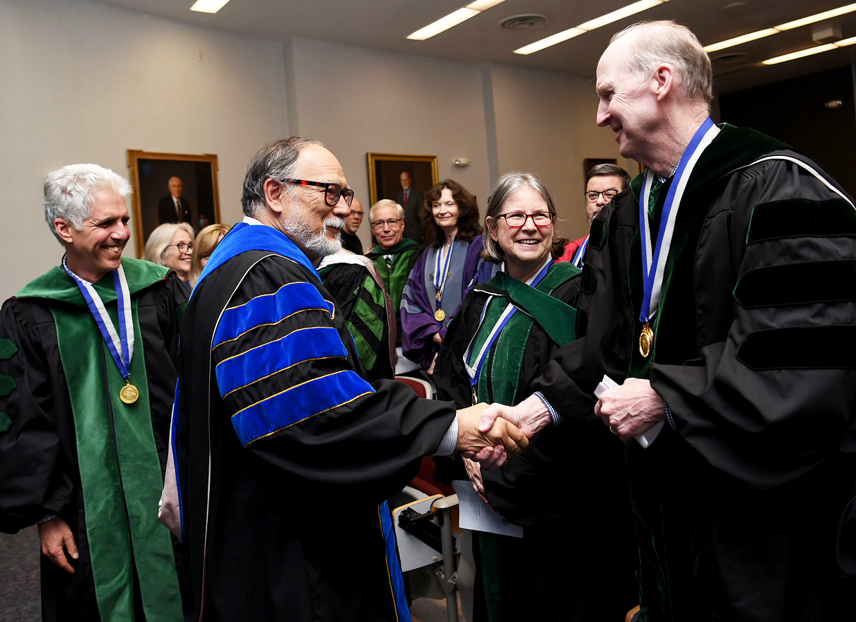 A group of people in academic regalia watch as two men shake hands.