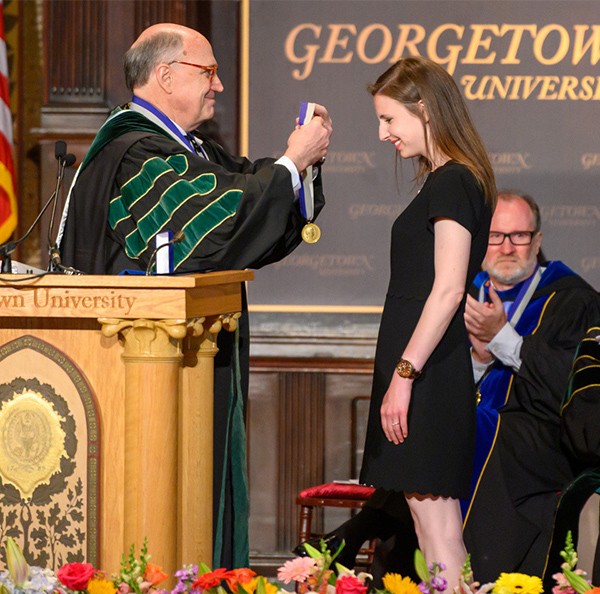 A woman accepts a medal from a man in academic regalia