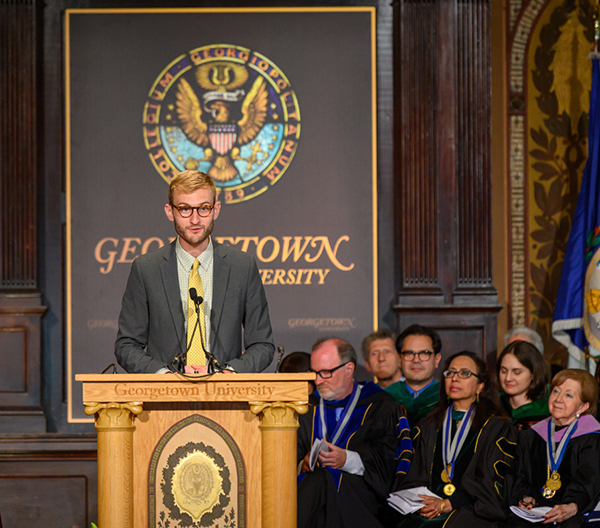 Billy Hoffman speaks at a podium while professors in academic regalia sit behind him