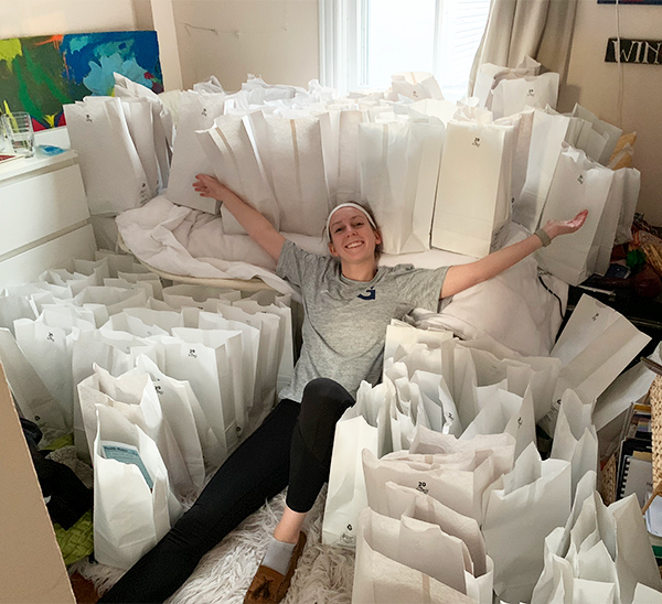 Hofley reclines with arms outstretched; she is surrounded by many white bags.