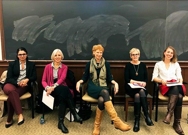 Five women sit in chairs in front of a blackboard