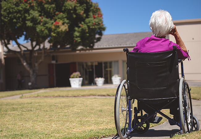 A woman sits in a wheelchair positioned in front of a nursing home facility
