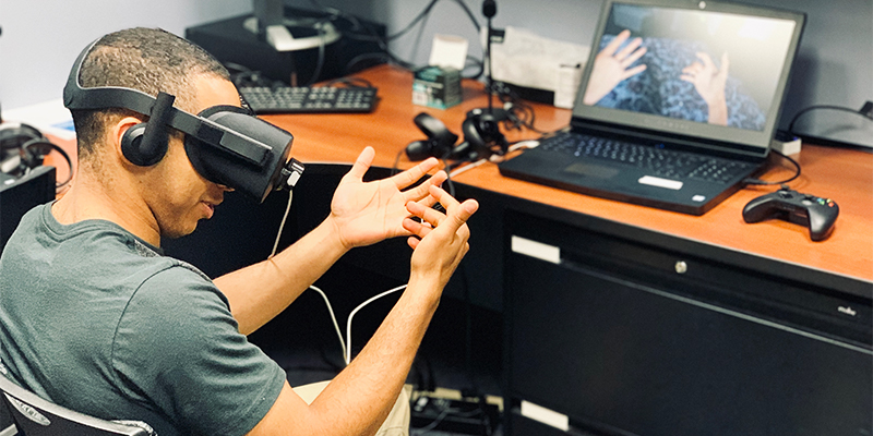 A person wearing virtual reality gear sits in a chair with hands raised before him in front of a computer screen