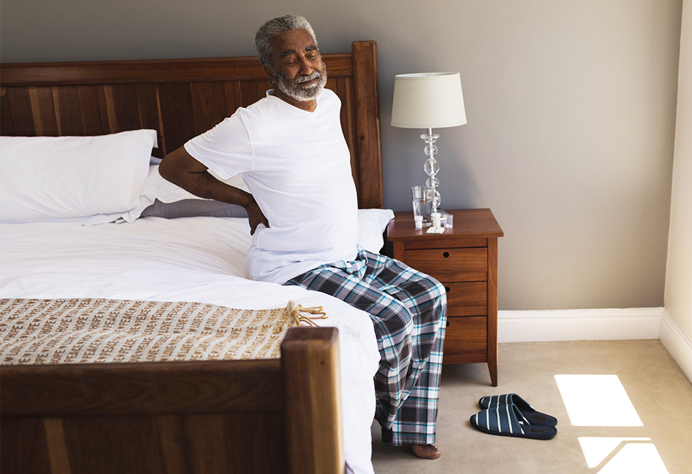 A man sits on a bed holding his back
