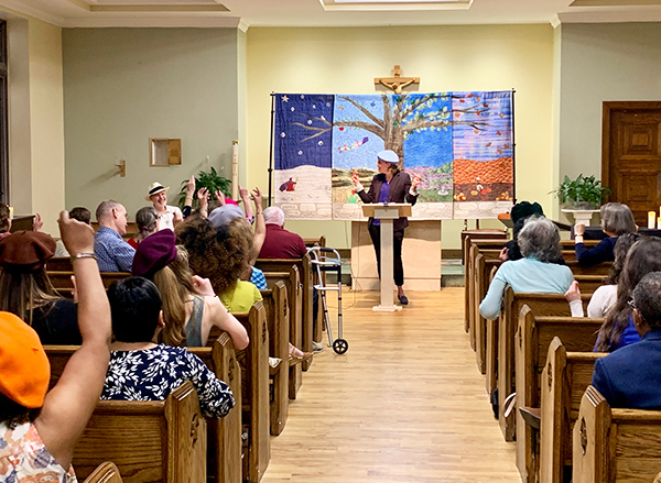 A woman stands at a podium before an audience seated in church pews