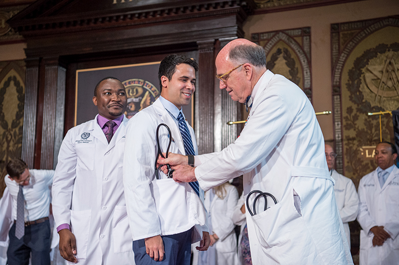 Dean Mitchell puts a stethoscope in the pocket of a medical student