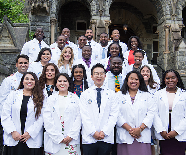 A group of medical students in their white coats stand for a photo on steps at Georgetown