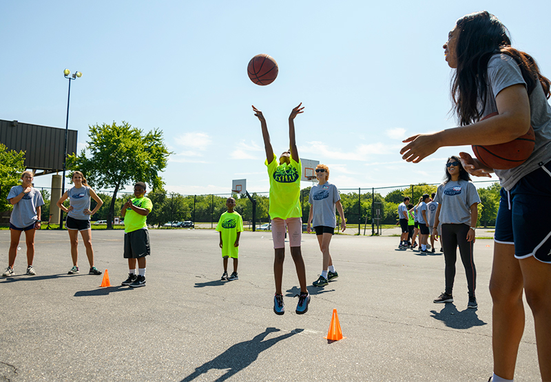 A child jumps for a basketball as camp counselors look on