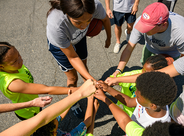 A group of children and young adults extend fists in a show of solidarity