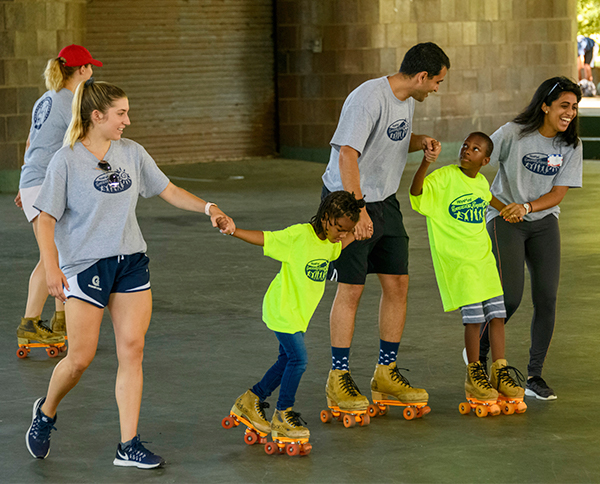 Camp counselors hold the hands of young campers roller-skating tentatively at an outdoor skate park