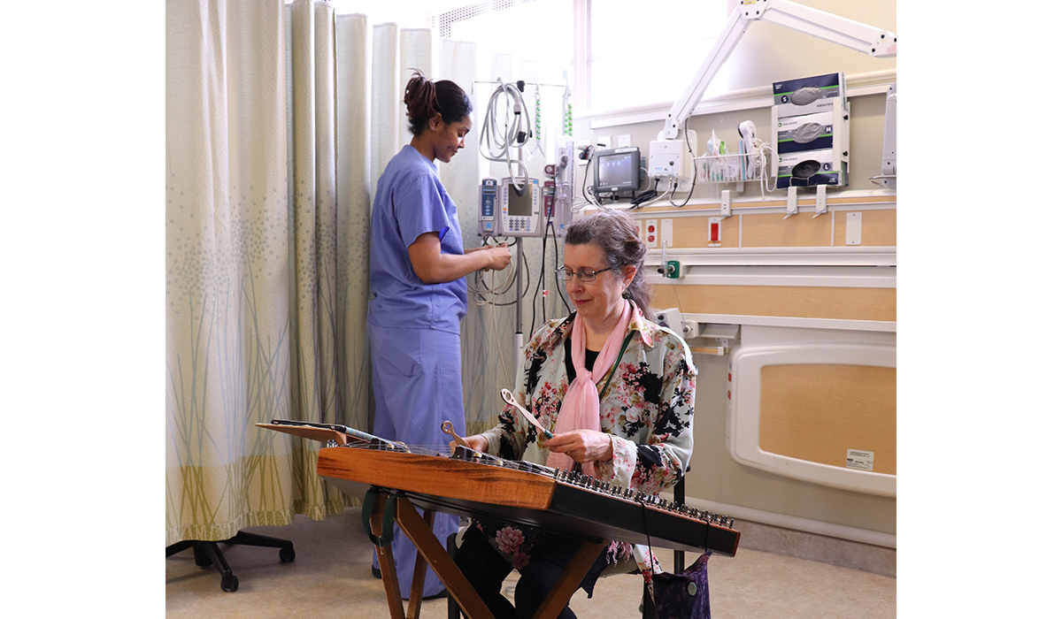 A woman sits and plays a hammered dulcimer; behind her a woman in scrubs works at a counter