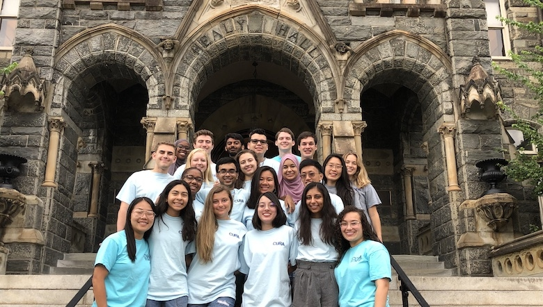 A group of students stand on the steps of Healey Hall