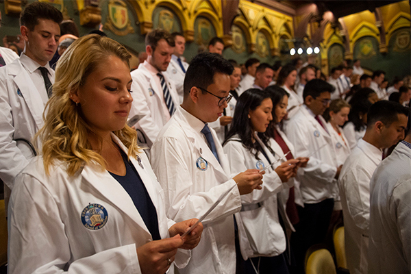 White coated medical students stand and read the Hippocratic Oath.