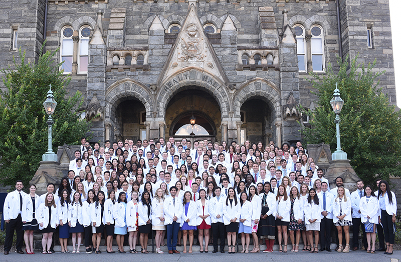 A large group of white coated medical students stands outside Healy Hall