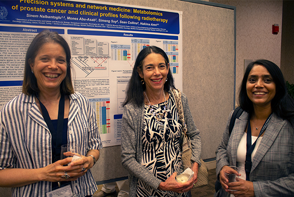 Three conference attendees stand in front of a poster