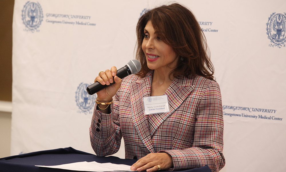 Nady Golestanah speaks from a podium