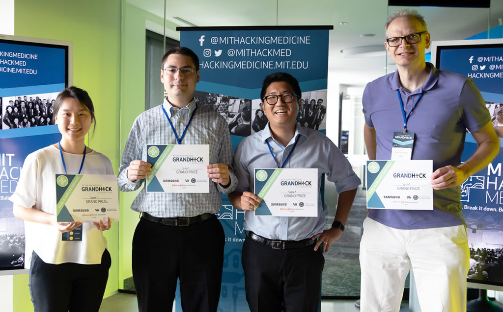 Four individuals stand together holding certificates