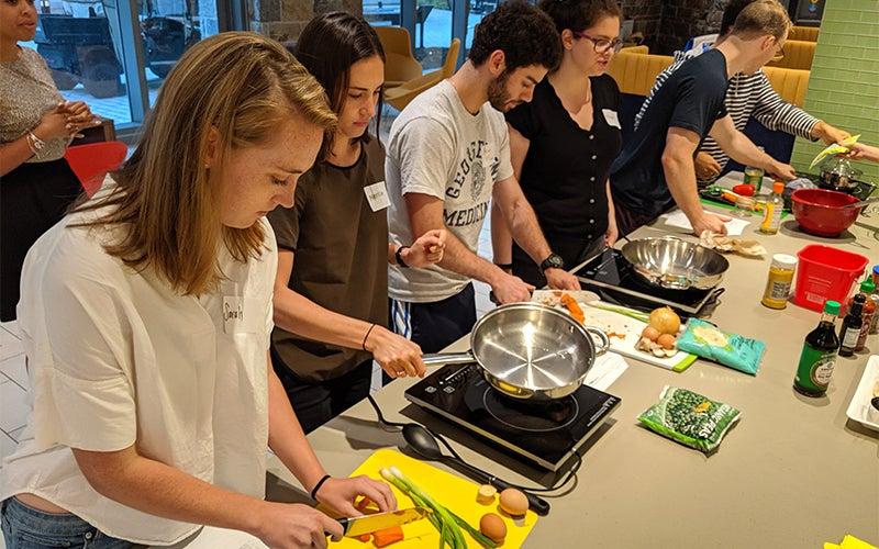 Individuals prepare food at a long counter