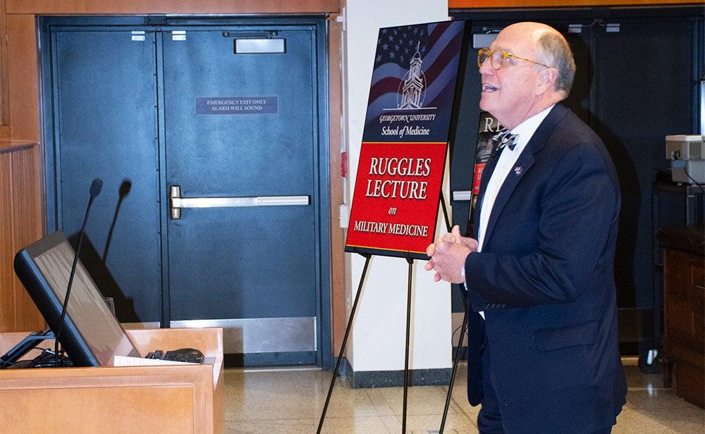 Dr. Mitchell speaks behind a podium