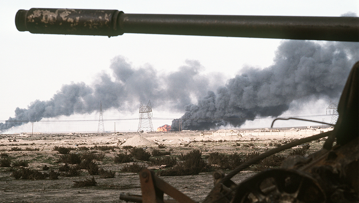 Landscape in Iraq punctuated by fire and smoke, a tank barrel is in the foreground