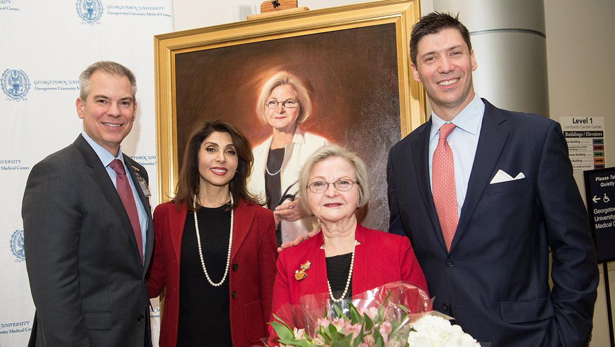 Four people stand together in front of a portrait