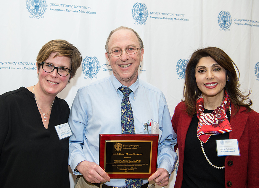 Three people stand together, the person in the middle holds a plaque