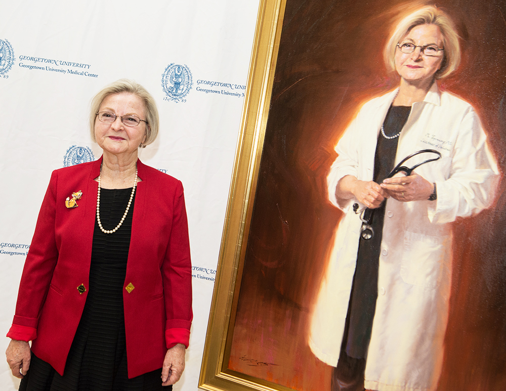 Dr. Toporowicz stands next to her portrait