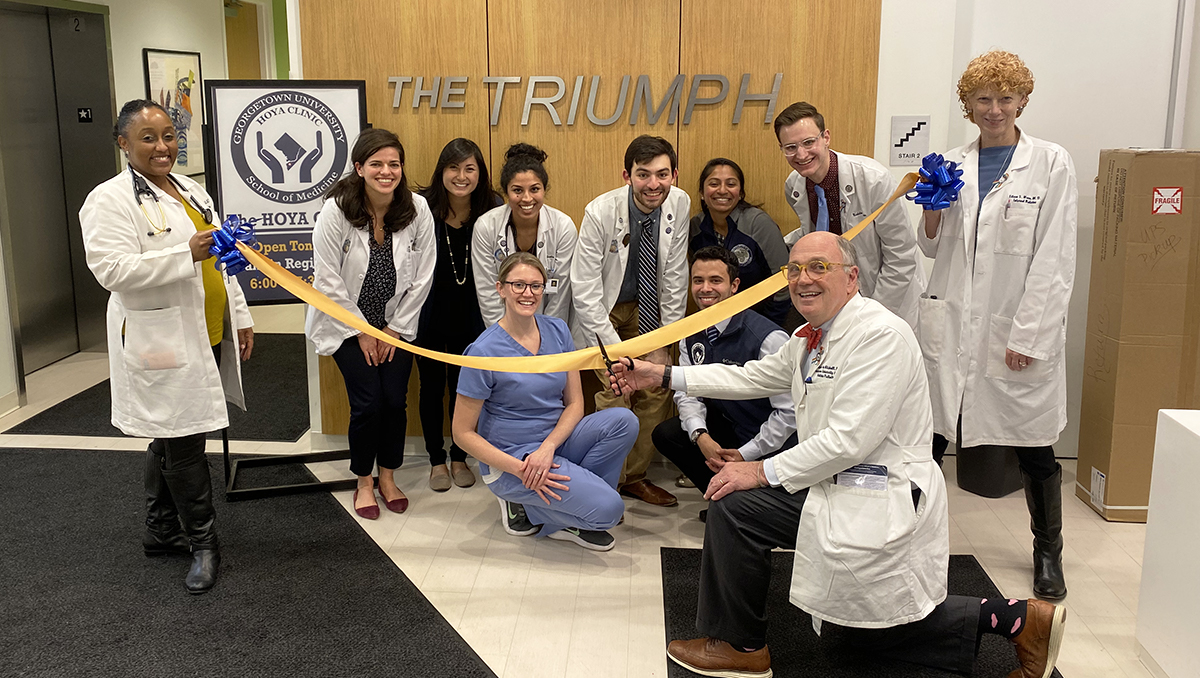 A group of people pose together at a ceremonial ribbon-cutting at The Triumph shelter