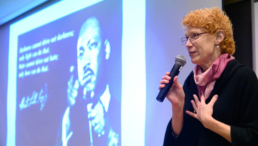 Eileen Moore speaks before a screen on which an image of Martin Luther King Jr. is projected