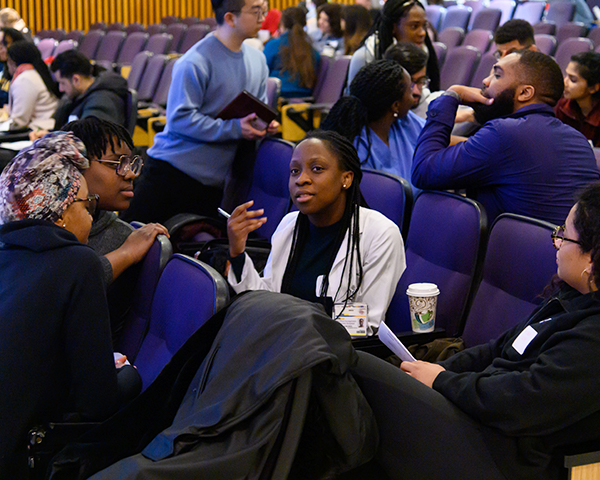 Groups of students talk in an auditorium