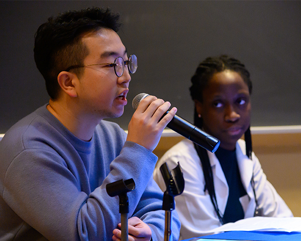 Two people sit at a table, one speaks into a microphone as the other looks on