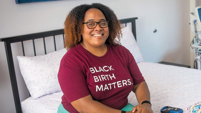 Ebony Marcelle (NHS'05) sits on a bed in a birthing suite