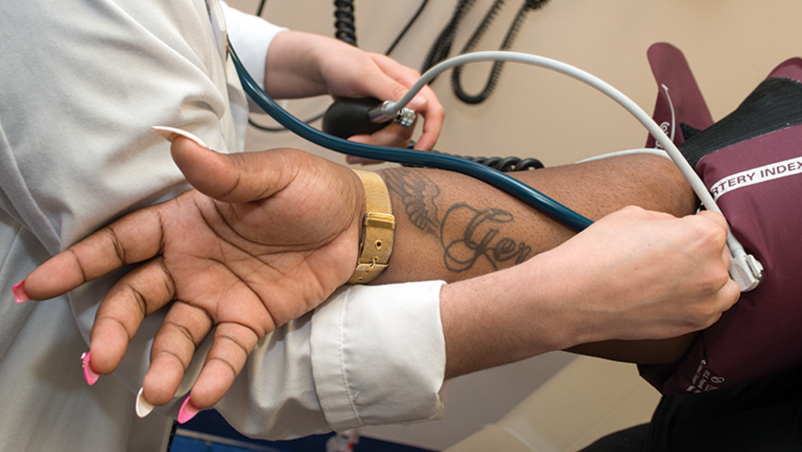 A person receives a blood pressure check from a student doctor
