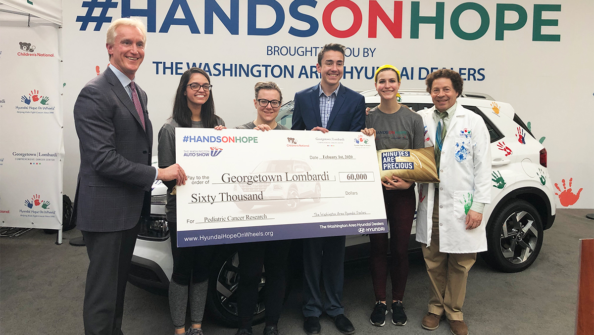 A group of people hold a large check in front of a car