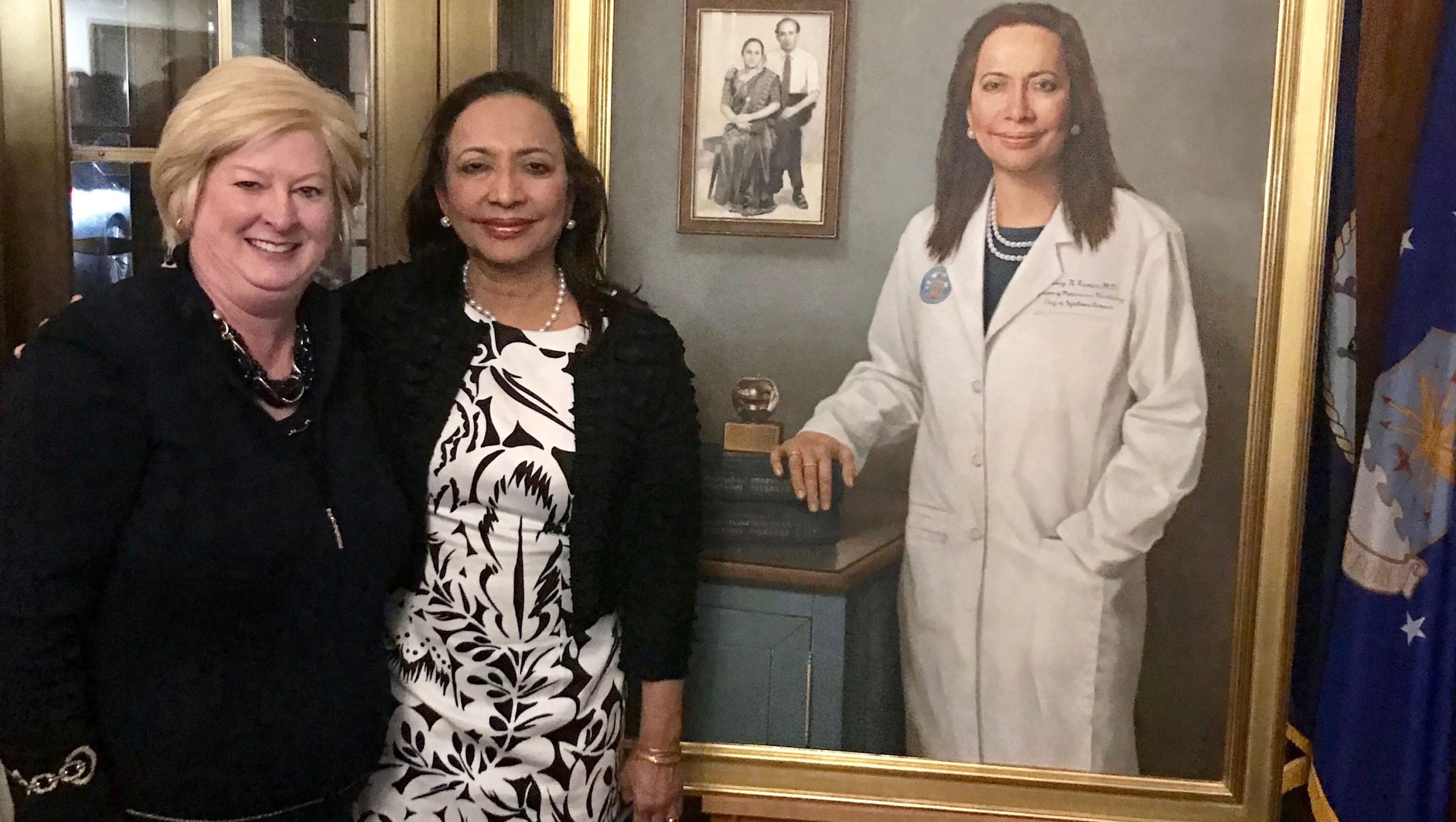 Two women stand side by side in front of a painting