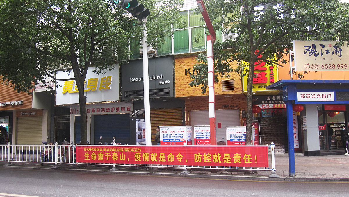 A street in Wuhan China empty but for a red banner along the roadside