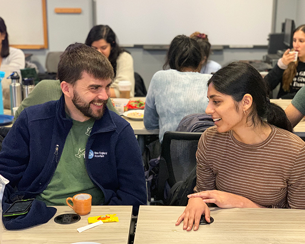 Blake Hite and Nitika Gupta talk with each other amid tables of classmates.