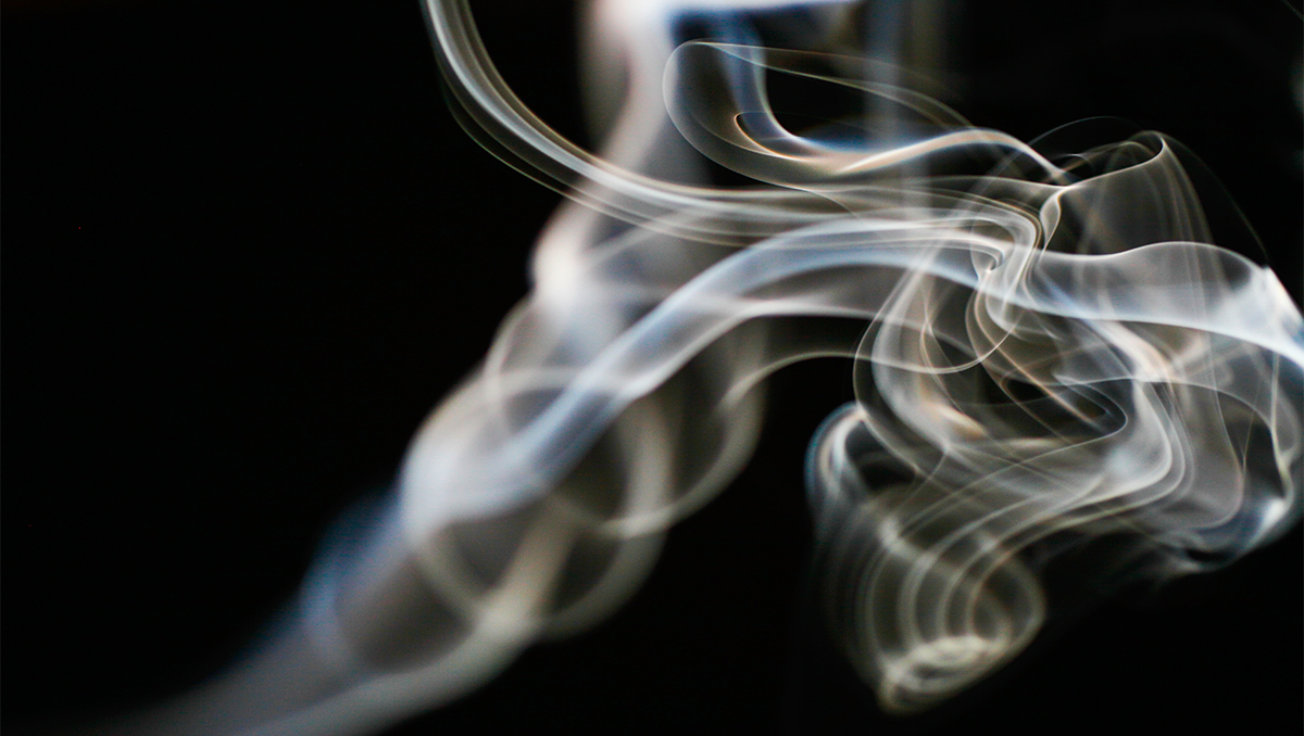 smoke from an unseen cigarette curls against a black background
