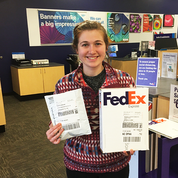 Melissa Baker holds boxes she is mailing at FedEx